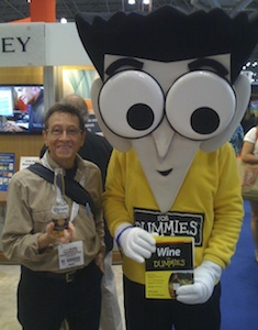 "A. D. Coleman hoists a brewski with the ""Wine for Dummies"" mascot, BookExpo America, Javits Center, NY, May2 29, 2013. Photographer unknown. Copyright 2013 by A. D. Coleman."