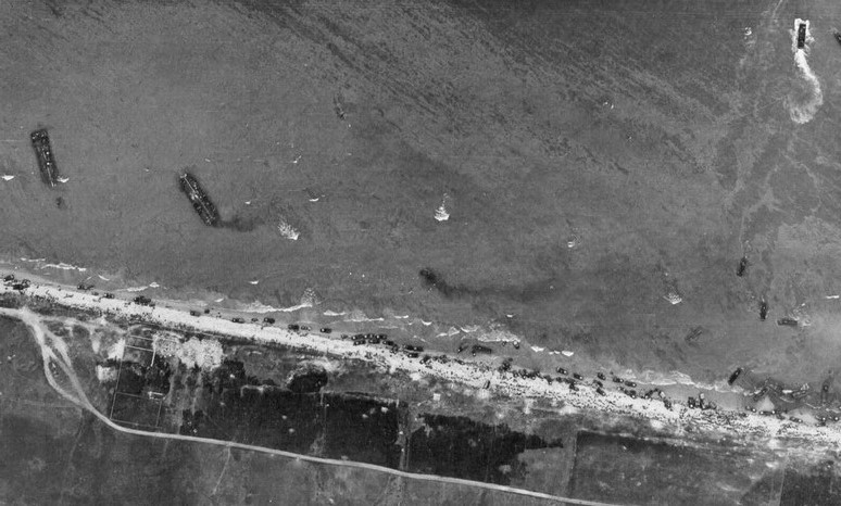 Aerial view of Omaha Beach, Normandy, France, taken 6 June 1944, showing landing of two infantry regiments, 18th and 115th, vehicles, and landing craft. Photo by U.S. Army, courtesy U.S. National Archives.