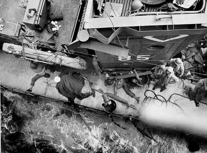 The mortally damaged USS LCI(L)-85, her decks littered with the dead, lays alongside the attack transport USS Samuel Chase (APA-26). Her crew managed to disembark the survivors before sinking. Note how the censor scratched off the dead soldier's face.  USCG photo, 6 June 1944.