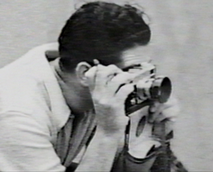 Robert Capa with Contax II. Photographer unknown, date unknown.