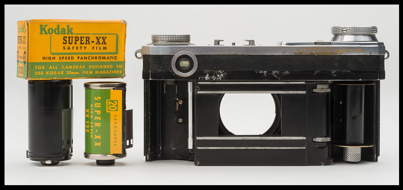 A Zeiss Ikon reloadable film cassette and a roll of Kodak Super-XX 35mm film sit next to a Contax II camera, the model used by Robert Capa on D-Day. (Note difference in height of cassettes.) Photo © 2015 by Rob McElroy.