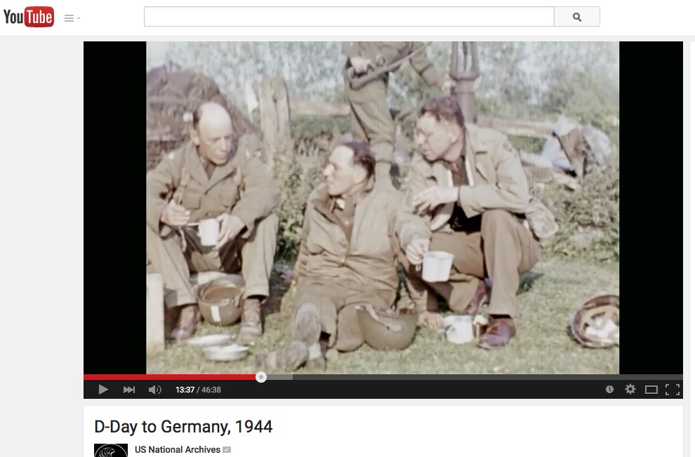 "Bob Landry (r), with shoes, Sainte-Mère-Église, as seen in Jack Lieb's film, ""D-Day to Germany, 1944."""