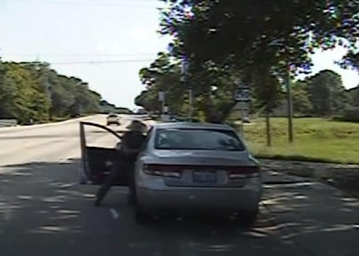 Texas State Trooper Brian Encinia reaches into Sandra Bland's car during their confrontation on July 10, 2015. Dashcam video screenshot.