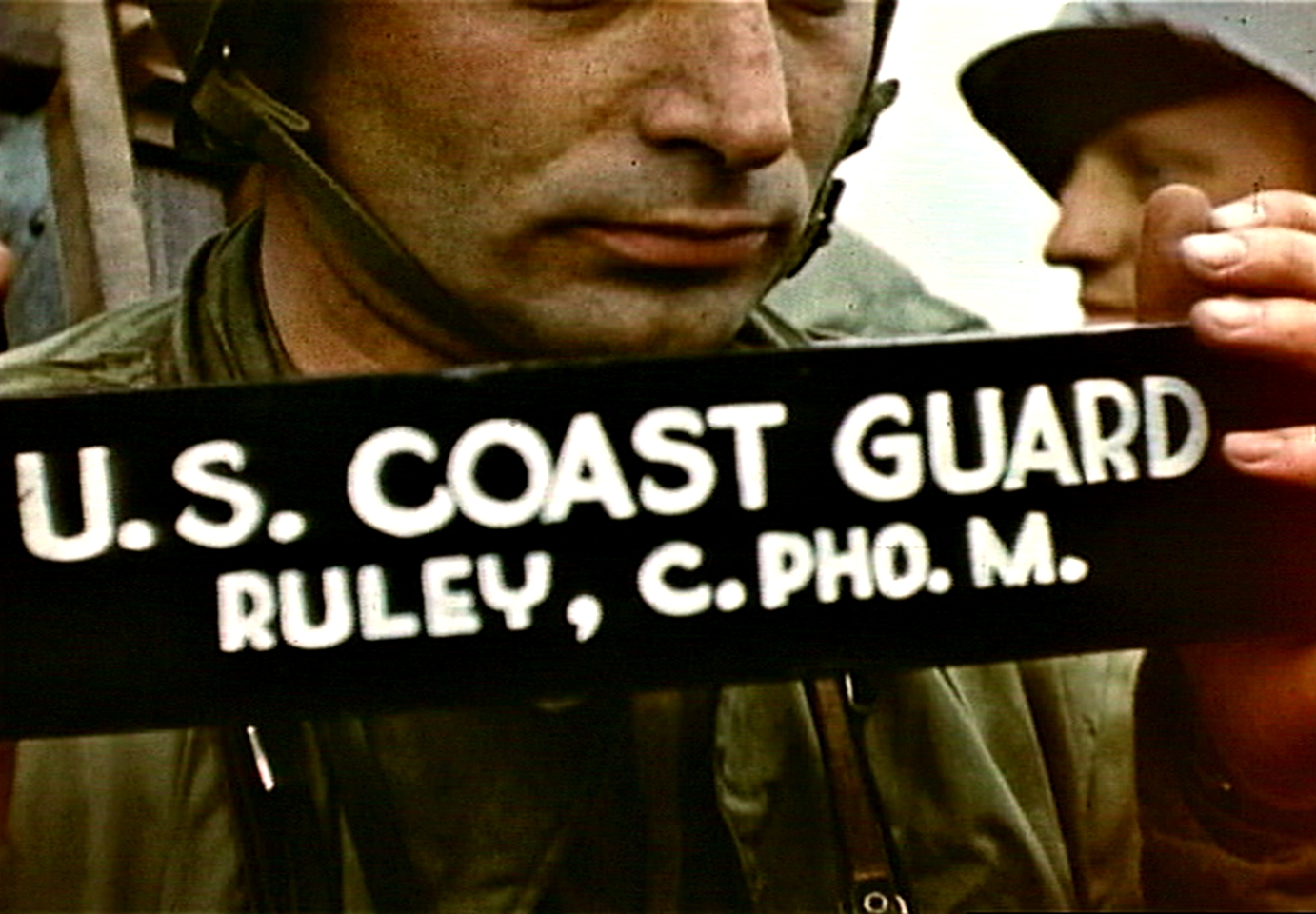 Fig. 10: Robert Capa holding cinematographer's slate aboard LCI(L)-94, D-Day, frame from film by David T. Ruley