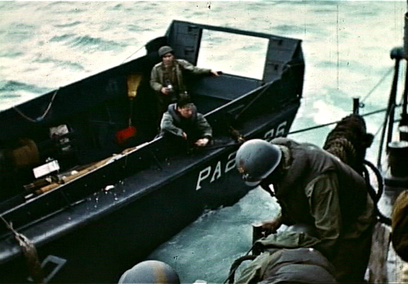 Fig. 12: Robert Capa, center rear, aboatd LCVP from USS Chase, photographing transfer of casualty, D-Day, frame from film by David T. Ruley
