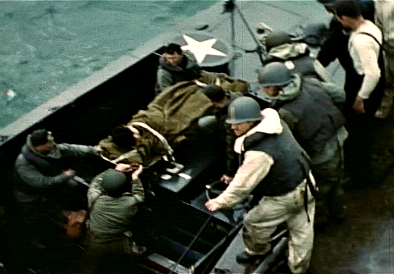 Fig. 14: Robert Capa, bottom left, aboard LCVP from USS Samuel Chase, assisting with transfer of casualty, D-Day, frame from film by David T. Ruley