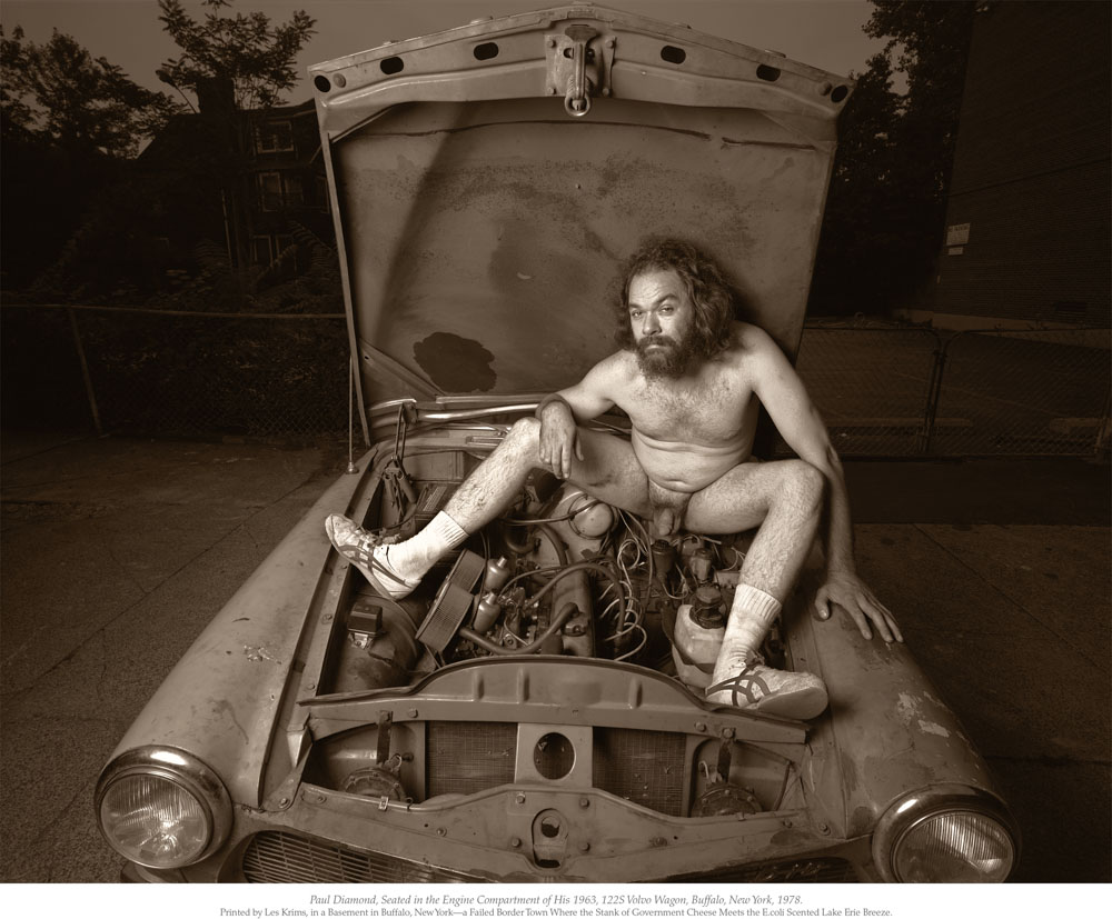 "Les Krims, ""Paul Diamond seated in the engine compartment of his 1963, 122S Volvo Wagon,"" Buffalo, New York, 1978"